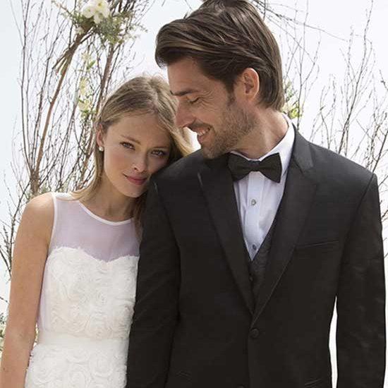 Wedding photo of groom wearing a Michael Kors tuxedo and bride